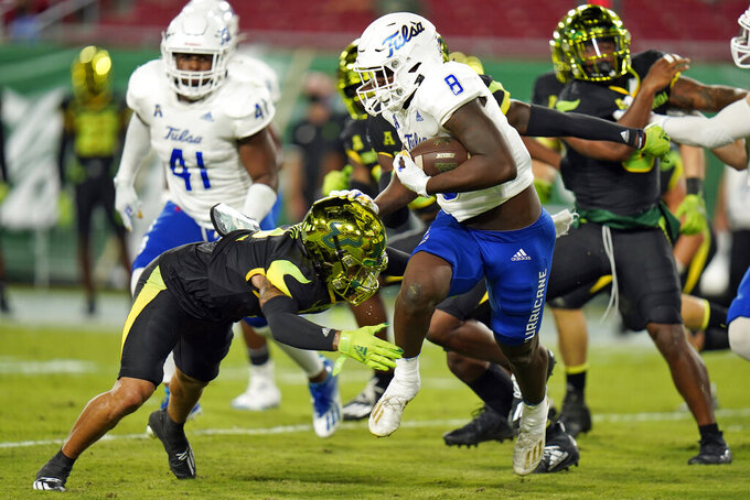 Tulsa running back Deneric Prince (8) eludes a tackle by South Florida defensive back Nick Roberts (2) during the first half of an NCAA college football game Friday, Oct. 23, 2020, in Tampa, Fla. (AP Photo/Chris O'Meara)