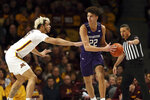 Northwestern's Pete Nance (22) looks to pass the ball against Minnesota's Jarvis Omersa during an NCAA college basketball game Sunday, Jan. 5, 2020, in Minneapolis. (AP Photo/Stacy Bengs)