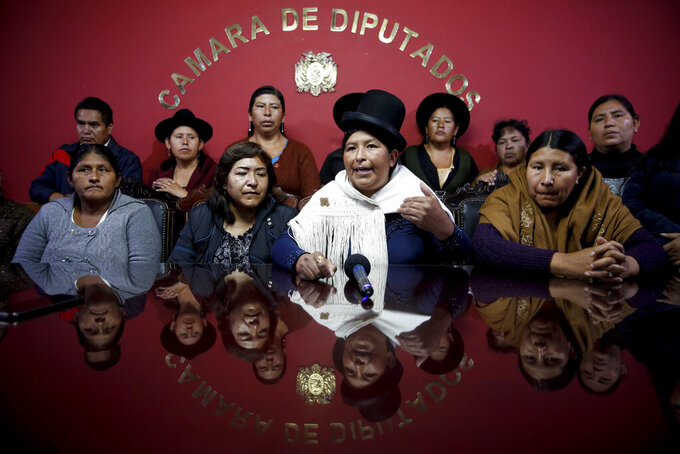 In this Tuesday, Nov. 19, 2019 photo, Movement Toward Socialism, MAS, legislators Juana Quispe, front row, from left; Bridge Quiroga, Concepcion Ortiz and Ayda Villarroel, meet with The Associated Press in the Chamber of Deputies, in La Paz, Bolivia. MAS lawmakers loyal to former President Evo Morales have majority in congress. Bolivia is wracked by civil unrest following the resignation of Morales, who fled to Mexico, over a disputed election. (AP Photo/Natacha Pisarenko)