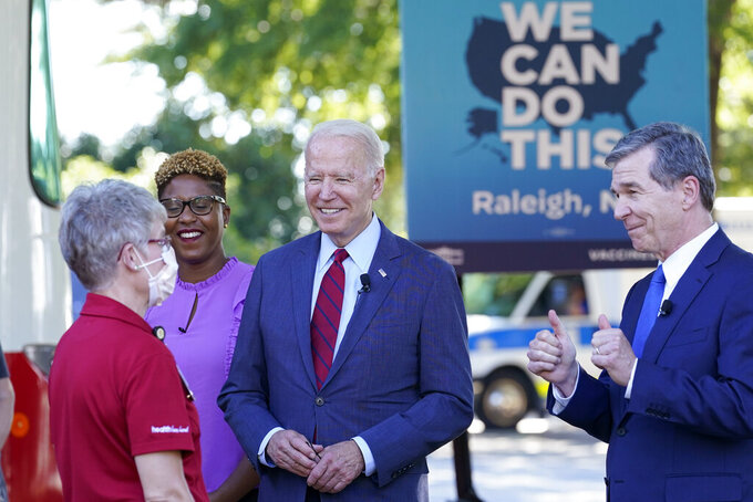 Dr. Rasheeda Monroe, medical director at Primary Care Pediatrics at WakeMed, listens as President Joe Biden and North Carolina Gov. Roy Cooper talk during a visit to a mobile vaccination unit at the Green Road Community Center in Raleigh, N.C., Thursday, June 24, 2021. (AP Photo/Susan Walsh)