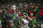 In this Feb. 6, 2019 photo, the wife of a soldier who was part of the group that attacked the presidential palace in a failed 1992 military coup organized by the late Hugo Chavez, checks her hair minutes before the start of the weekly, live TV program coined: