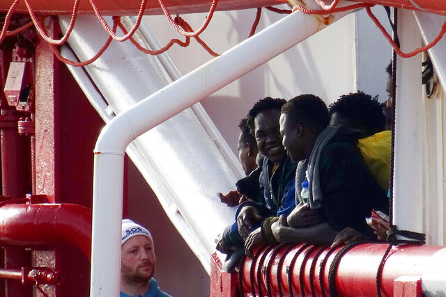 People wait to disembark from the Ocean Viking rescue ship, at the Taranto harbor, Southern Italy, Wednesday, Jan. 29, 2020.  The SOS Mediterranee NGO ship disembarked 403 migrants rescued over the weekend in the Mediterranean Sea. (Ingenito/LaPresse via AP)