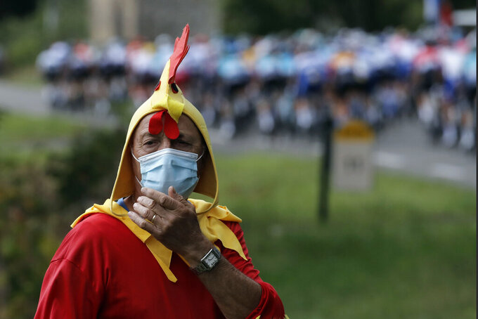 A spectator dressed up as a rooster stands along the road of the ninth stage of the Tour de France cycling race over 153 kilometers (95 miles), with start in Pau and finish in Laruns, Sunday, Sept. 6, 2020. (AP Photo/Christophe Ena)