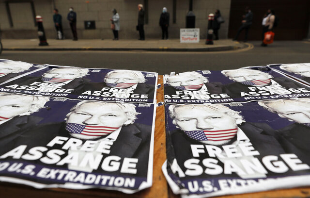 People queue at the entrance of the Old Bailey court in London, Monday, Sept. 21, 2020, as the Julian Assange extradition hearing to the US continues. (AP Photo/Frank Augstein)