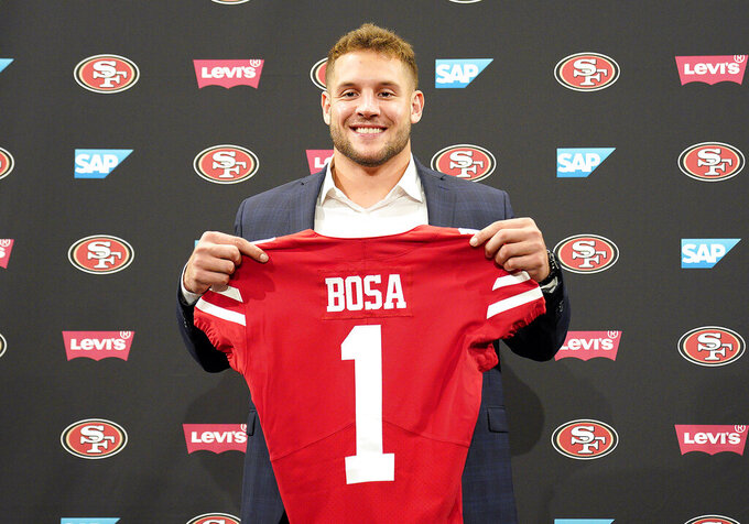 San Francisco 49ers first-round pick Nick Bosa poses with his jersey during an NFL football news conference, Friday, April 26, 2019, in Santa Clara, Calif. (AP Photo/Tony Avelar )