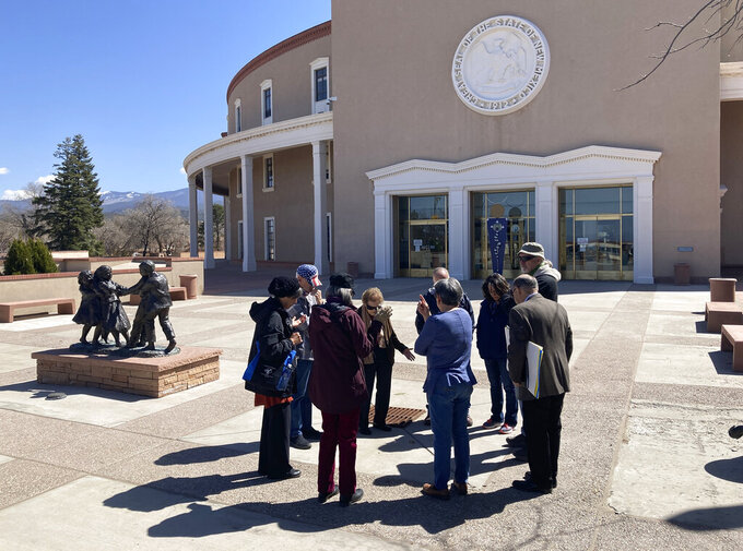 A Christian group prays that outside the state capitol building on Tuesday, March 30, 2021, in Santa Fe, New Mexico. Legislators met in a special session to revisit a sprawling set of marijuana legalization proposals that led to a deadlock during the regular session earlier in March. (AP Photo/Cedar Attanasio)