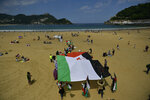 Saharan demonstrator wave their flags as they take part in a rally along the Concha beach support Brahim Gali, leader of the Polisario Front and a Sahara free, in San Sebastian, northern Spain, Sunday, May 30, 2021. Brahim Gali is recovering from COVID-19 in a Spanish hospital. The leader of the Western Sahara independence movement at the heart of a diplomatic spat between Spain and Morocco will appear before an investigating judge in Spain on June 1. (AP Photo/Alvaro Barrientos)