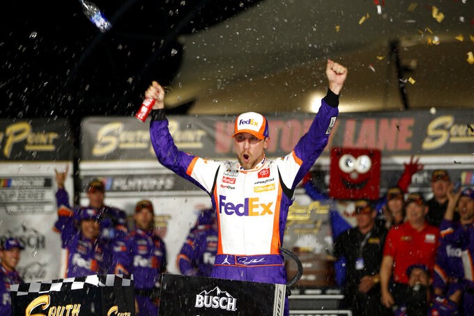 NASCAR Cup Series driver Denny Hamlin (11) celebrates in victory lane after winning a NASCAR Cup Series auto race at the Las Vegas Motor Speedway, Sunday, Sept. 26, 2021, in Las Vegas. (AP Photo/Steve Marcus)