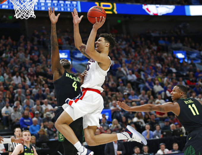 Gonzaga forward Brandon Clarke, center, goes to the basket as Baylor's Mario Kegler (4) and Mark Vital (11) defend during the second half of a second-round game in the NCAA men's college basketball tournament Saturday, March 23, 2019, in Salt Lake City. (AP Photo/Rick Bowmer)