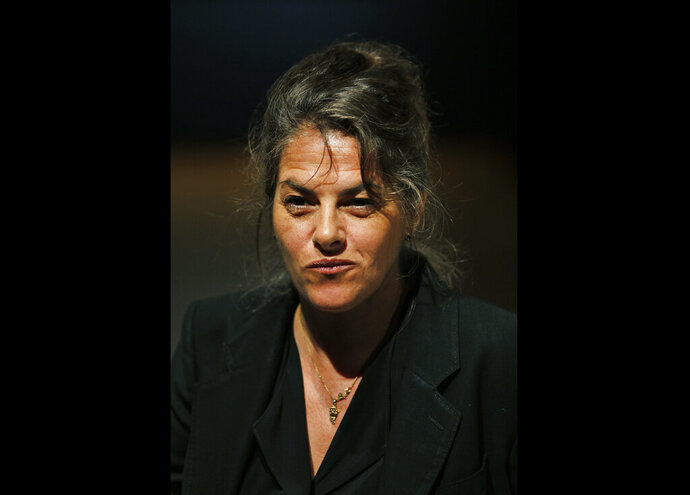 FILE - In this Friday, June 27, 2014 file photo, British artist Tracey Emin poses for photographers next to her 1998 artpiece, entitled 'My Bed' at an auction house exhibition space in central London. British artist Tracey Emin says she was diagnosed with cancer earlier this year and is in remission after an operation. In an interview published Wednesday, Oct. 28, 2020, Emin told the website Artnet that a malignant tumor was discovered on her bladder in the spring.  (AP Photo/Lefteris Pitarakis, file)