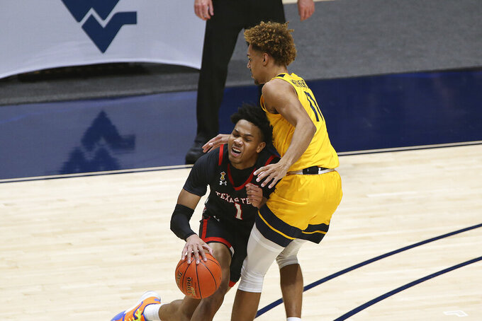 Texas Tech guard Terrence Shannon Jr. (1) is defended by West Virginia forward Emmitt Matthews Jr. (11) during the first half of an NCAA college basketball game Monday, Jan. 25, 2021, in Morgantown, W.Va. (AP Photo/Kathleen Batten)