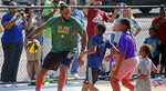 LeBron James is triple-teamed by I Promise School students during a pickup game of basketball during the debut of the new basketball court at the school Wednesday, Aug. 14, 2019 in Akron, Ohio. James dedicated a basketball court at the school he founded for underprivileged children in his hometown. (Jeff Lange/Akron Beacon Journal via AP)