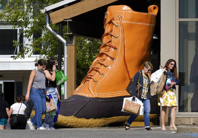Shoppers walk past a giant LL Bean boot outside the Ross Park Mall in Pittsburgh Sunday, May 23, 2021. With vaccinations rolling out and shoppers freer to go out maskless, retailers are seeing an eager return to their stores after months of watching their customers focus on online buying during the pandemic. (AP Photo/Gene J. Puskar)