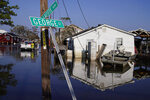 """Nathan Fabre, left, and Shannon Lation check on their home and boat destroyed by Hurricane Ida, Sunday, Sept. 5, 2021, in Lafitte, La. """"We lost everything,"""" said Fabre about the destruction of his home. (AP Photo/John Locher)"""
