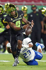 South Florida quarterback Noah Johnson (0) fumbles the football after getting hit by Tulsa linebacker Zaven Collins (23) during the first half of an NCAA college football game Friday, Oct. 23, 2020, in Tampa, Fla. Tulsa recovered the fumble. (AP Photo/Chris O'Meara)