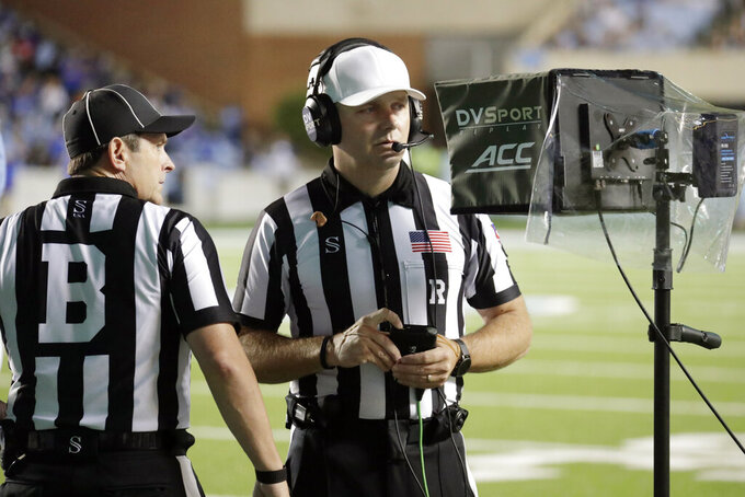 Officials review a touchdown by Georgia State during the first half of an NCAA college football game against North Carolina in Chapel Hill, N.C., Saturday, Sept. 11, 2021. They ruled that the touchdown call on the field was correct. (AP Photo/Chris Seward)