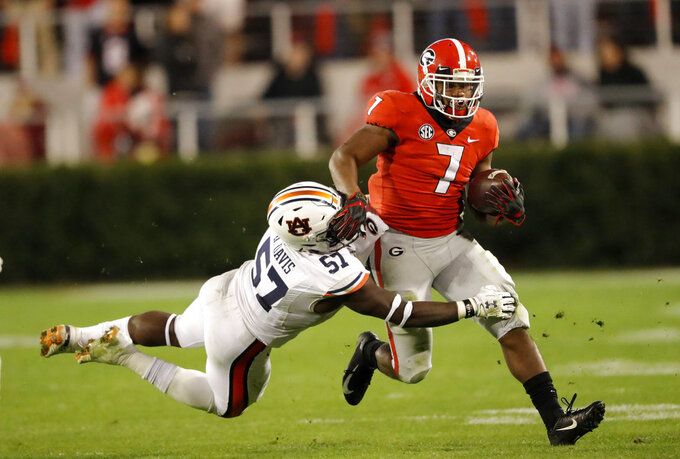 Georgia running back D'Andre Swift (7) tries to get away from Auburn linebacker Deshaun Davis (57) during the second half of an NCAA college football game Saturday, Nov. 10, 2018, in Athens, Ga. (AP Photo/John Bazemore)