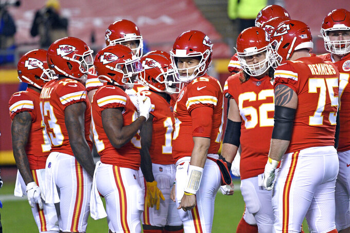 Kansas City Chiefs quarterback Patrick Mahomes (15) stands with teammates in the huddle during the first half of the AFC championship NFL football game against the Buffalo Bills, Sunday, Jan. 24, 2021, in Kansas City, Mo. (AP Photo/Reed Hoffmann)