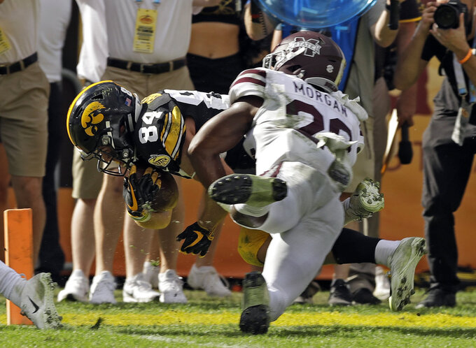 Iowa wide receiver Nick Easley (84) is hit by Mississippi State safety C.J. Morgan as he scores a touchdown during the second half of the Outback Bowl NCAA college football game Tuesday, Jan. 1, 2019, in Tampa, Fla. (AP Photo/Chris O'Meara)