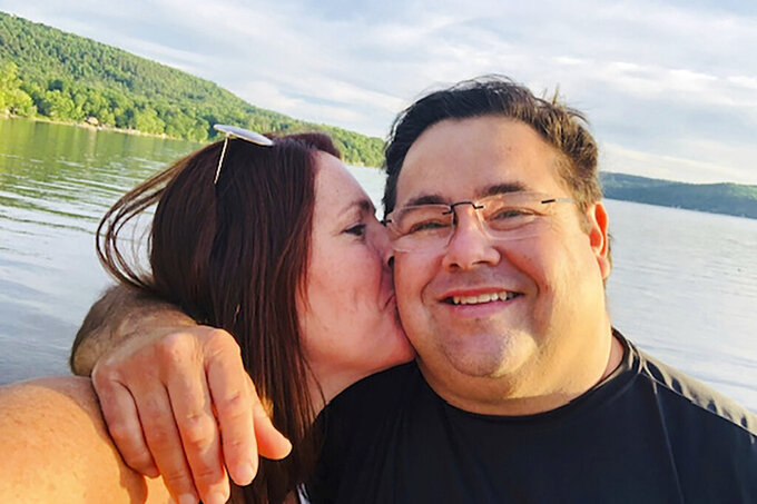 In this undated photo made available by Karyn Arellano, she kisses her husband Alan. Alan Arellano, 49, died after suffering a heart attack while being treated for COVID-19. (Karyn Arellano via AP)