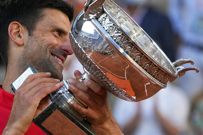 Serbia's Novak Djokovic smiles while holding the cup after defeating Stefanos Tsitsipas of Greece during their final match of the French Open tennis tournament at the Roland Garros stadium Sunday, June 13, 2021 in Paris. Djokovic won 6-7 (6), 2-6, 6-3, 6-2, 6-4. (AP Photo/Michel Euler)