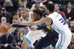 Indiana Pacers' Wesley Matthews, center, goes for a loose ball against Charlotte Hornets' Nicolas Batum, left, and Jeremy Lamb, right, during the second half of an NBA basketball game, Monday, Feb. 11, 2019, in Indianapolis. Indiana won 99-90. (AP Photo/Darron Cummings)