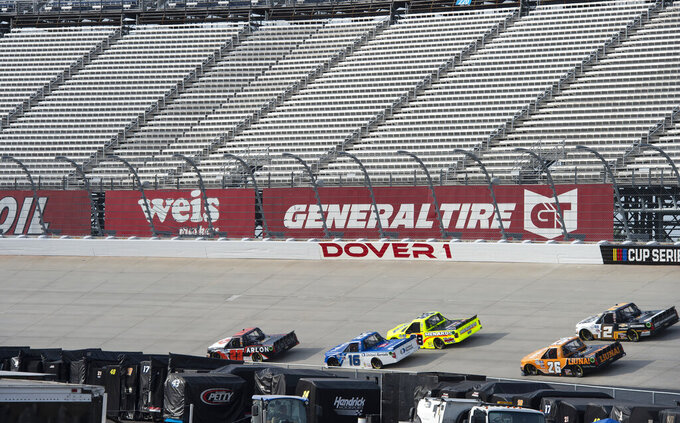 Trucks enter Turn 1 during a NASCAR Truck Series race at Dover International Speedway, Friday, Aug. 21, 2020, in Dover, Del. (AP Photo/Jason Minto)