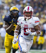 SMU running back Xavier Jones (5) rushes ahead of Michigan defensive lineman Rashan Gary, left, in the third quarter of an NCAA college football game in Ann Arbor, Mich., Saturday, Sept. 15, 2018. Michigan won 45-20. (AP Photo/Tony Ding)