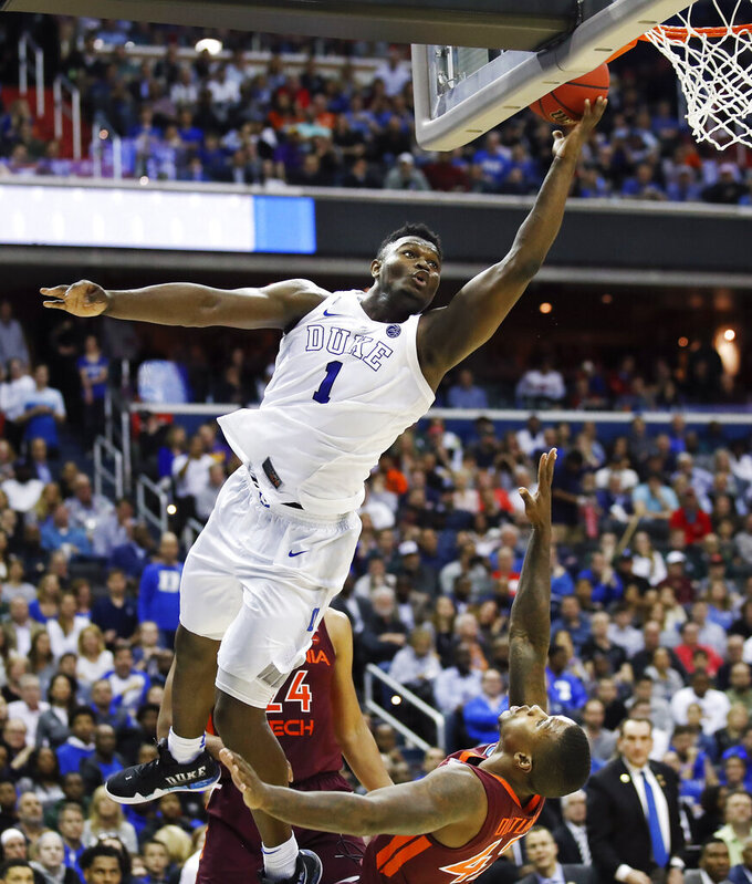 FILE - In this March 29, 2019, file photo, Duke forward Zion Williamson (1) drives to the basket to score on Virginia Tech's guard Ty Outlaw (42) during the second half of an NCAA men's college basketball tournament East Region semifinal in Washington.  Zion Williamson is the most hyped, most exciting prospect to come to the NBA in years. He's set to be the No. 1 pick in the draft, perhaps the only certainty heading into Thursday night, June 20. (AP Photo/Alex Brandon)