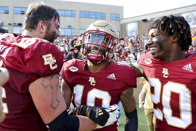 Boston College defensive back Brandon Sebastian (10) is on congratulate by teammates after making the game-ending interception in the overtime period of an NCAA college football game against Missouri, Saturday, Sept. 25, 2021, in Boston. (AP Photo/Mary Schwalm)
