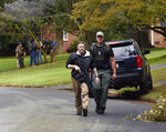 Law enforcement officers search the Foxhall neighborhood behind Mount Tabor High School in Winston-Salem, N.C., after a shooting that left one student dead, Wednesday, Sept. 1, 2021. (Walt Unks/The Winston-Salem Journal via AP)
