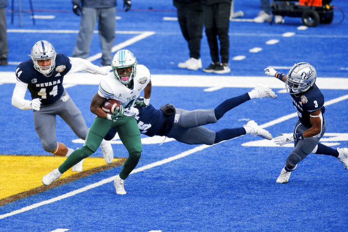 Tulane wide receiver Jha'Quan Jackson (4) spins out of a tackle attempt by Nevada defensive back AJ King (25) during the second half of the Idaho Potato Bowl NCAA college football game, Tuesday, Dec. 22, 2020, in Boise, Idaho. (AP Photo/Steve Conner)