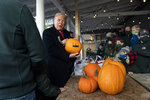President Donald Trump holds an autographed pumpkin during a visit to the Treworgy Family Orchards, Sunday, Oct. 25, 2020, in Levant, Maine.(AP Photo/Alex Brandon)