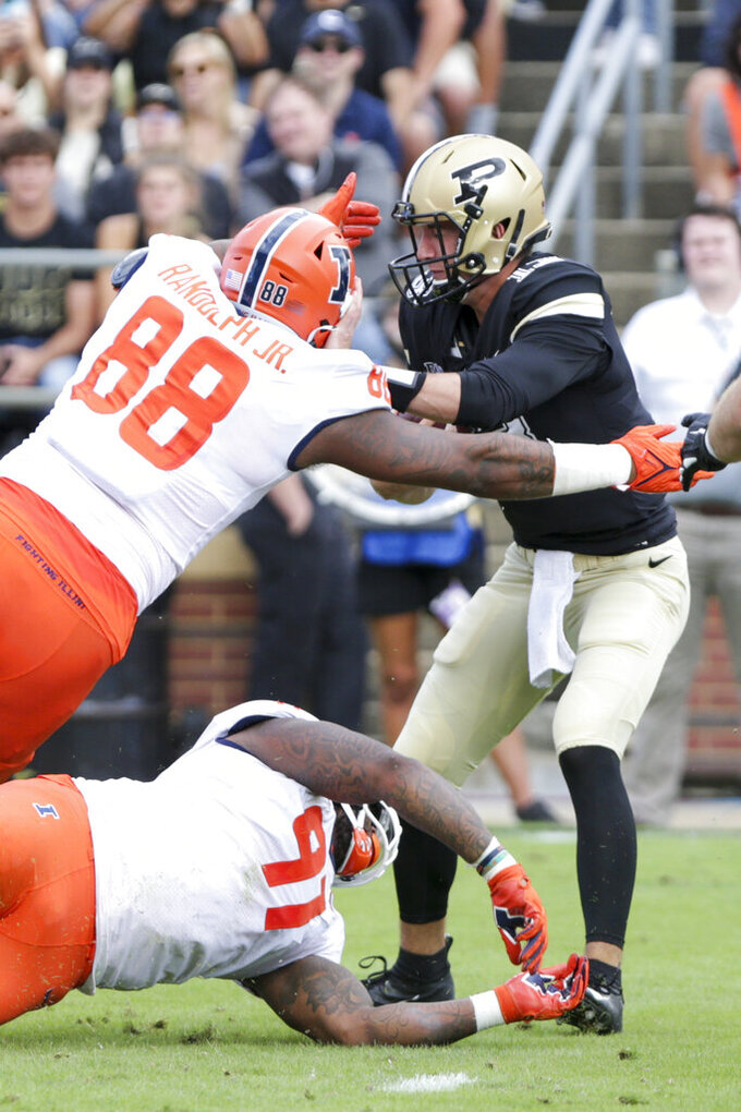 Purdue quarterback Jack Plummer (13) is tackled by Illinois defensive linemen Keith Randolph Jr. (88) and Jamal Woods (91) during the first quarter of an NCAA college football game, Saturday, Sept. 25, 2021, in West Lafayette, Ind. (Nikos Frazier/Journal & Courier via AP)