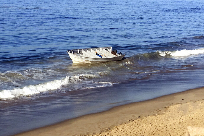 This Saturday, Sept. 14, 2019 photo released by the Ventura County Sheriff's Office shows a panga boat beached on the Southern California coast near Malibu. The Ventura County Sheriff's Office says the report came in shortly before dawn Saturday and deputies found a 35-foot panga boat on the shore below Pacific Coast Highway between Malibu and Point Mugu. In addition to 577 pounds of marijuana, investigators found 37 large containers filled with gasoline in the boat, floating in the water and on the beach. (Ventura County Sheriff's Office via AP)
