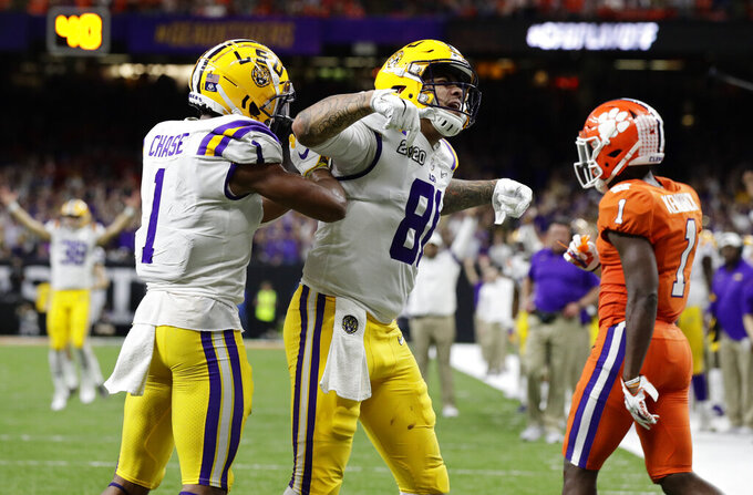 LSU tight end Thaddeus Moss, center, celebrates after scoring with wide receiver Ja'Marr Chase during the second half of a NCAA College Football Playoff national championship game against Clemson, Monday, Jan. 13, 2020, in New Orleans. (AP Photo/Sue Ogrocki)