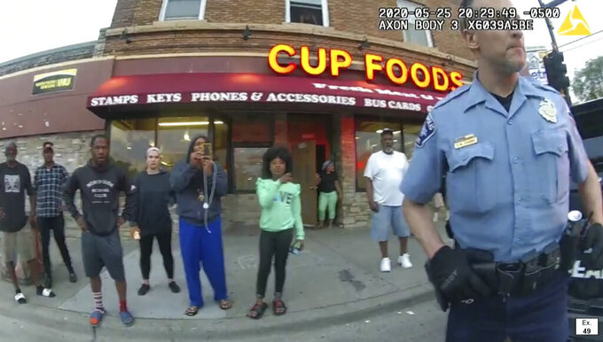 In this image from police body camera video former Minneapolis police Officer Derek Chauvin stands outside Cup Foods in Minneapolis, on May 25, 2020, with a crowd of onlookers behind him. The image was shown as prosecutor Steve Schleicher gave closing arguments as Hennepin County Judge PeterCahill presided Monday, April 19, 2021, at the Hennepin County Courthouse in Minneapolis, in the trial of Chauvin who is charged in the May 25 death of George Floyd. (Court TV via AP, Pool)