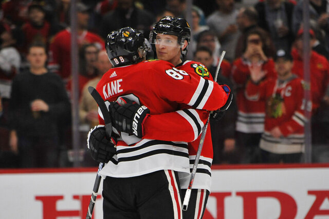Chicago Blackhawks' Patrick Kane (88) celebrates with teammate Dominick Kubalik (8) of the Czech Republic, after defeating the San Jose Sharks 6-2 in an NHL hockey game Wednesday, March 11, 2020, in Chicago. (AP Photo/Paul Beaty)
