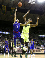 Kansas guard Devon Dotson (11) scores over Baylor forward Flo Thamba (0) in the first half of an NCAA college basketball game, Saturday, Jan. 12, 2019, in Waco, Texas. (AP Photo/Jerry Larson)