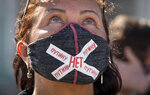 A woman wears a face mask to protect against coronavirus infection with a sign