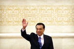 Chinese Premier Li Keqiang waves as he arrives for a press conference held after the closing session of China's National People's Congress (NPC) at the Great Hall of the People in Beijing, Friday, March 15, 2019. (AP Photo/Mark Schiefelbein)