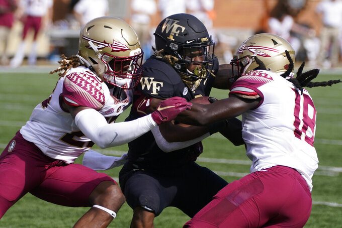 Wake Forest running back Christian Turner, center, is tackled by Florida State defensive back Sidney Williams, left, and defensive back Travis Jay during the first half of an NCAA college football game Saturday, Sept. 18, 2021, in Winston-Salem, N.C. (AP Photo/Chris Carlson)