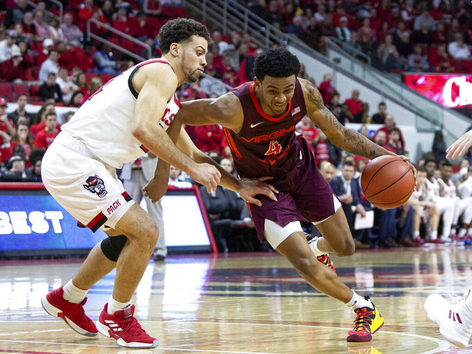 Virginia Tech's Nickeil Alexander-Walker (4) drives against North Carolina State's Devon Daniels, left, during the second half of an NCAA college basketball game in Raleigh, N.C., Saturday, Feb. 2, 2019. (AP Photo/Ben McKeown)