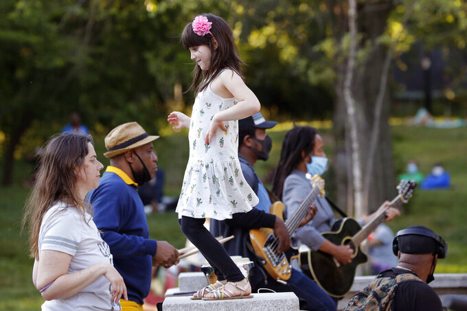 """In this Tuesday, June 16, 2020, photo, a young girl dances with her mother to the music of Alegba and Friends, a Haitian jazz and roots band performing nightly free concerts at Prospect Park's landmark boathouse in New York. The band's leader, Alegba Jahyile, who is Haitian, says, """"When people come here, they come to have a little good time, to have a picnic with their family, their friends, their lovers. And then the music takes them to another level."""" Jahyile says he's seen people respond to his music, so he intends to continue the concerts """"until the next snowflakes fall."""" (AP Photo/Kathy Willens)"""