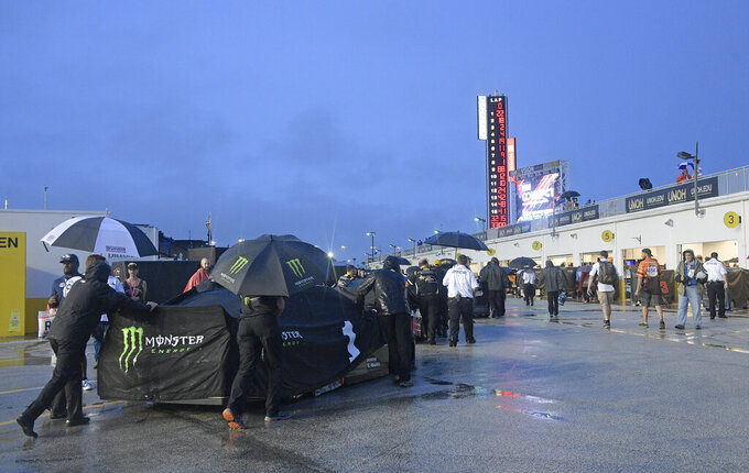 Kurt Busch's crew moves his car back to the garages after a NASCAR Cup Series auto race was postponed because of inclement weather at Daytona International Speedway, Saturday, July 6, 2019, in Daytona Beach, Fla. The race was rescheduled for Sunday. (AP Photo/Phelan Ebenhack)