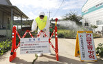 A quarantine official wearing protective gear places a barricade as a precaution against African swine fever at a pig farm in Paju, South Korea, Tuesday, Sept. 17, 2019. South Korea is culling thousands of pigs after confirming African swine fever at a farm near its border with North Korea, which had an outbreak in May. The notice reads: