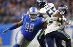 "FILE - In this Oct. 28, 2018, file photo, Detroit Lions defensive tackle Damon Harrison (98) tackles Seattle Seahawks running back Chris Carson (32) during an NFL football game in Detroit. The Detroit Lions have signed defensive tackle Damon ""Snacks"" Harrison to an $11 million, one-year extension. The team announced the signing Thursday, Aug. 22, 2019. (AP Photo/Paul Sancya, File)"