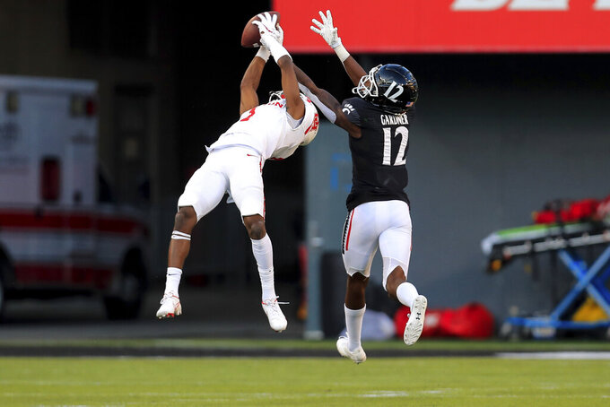 Houston wide receiver Bryson Smith, left, makes a catch against Cincinnati cornerback Ahmad Gardner, right, during the first half of an NCAA college football game, Saturday, Nov. 7, 2020, in Cincinnati. (AP Photo/Aaron Doster)
