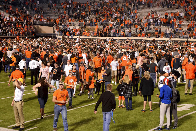 Oklahoma State fans take to the field following an NCAA college football game against Texas, in Stillwater, Okla., Saturday, Oct. 27, 2018. Oklahoma State defeated Texas 38-35. (AP Photo/Brody Schmidt)