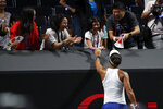 Naomi Osaka of Japan passes a tennis ball to her fans after defeating Petra Kvitova of the Czech Republic in their WTA Finals Tennis Tournament in Shenzhen, China's Guangdong province, Sunday, Oct. 27, 2019. (AP Photo/Andy Wong)